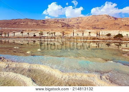 Living Water of the Dead Sea, Israel. Between the sea and dry mountains of red sandstone highway passes. Midday heat evaporates water. The concept of medical and ecological tourism