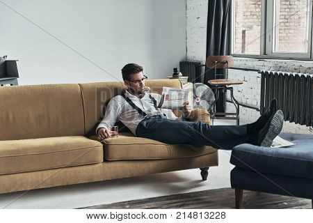 What is new in the world? Stylishly dressed young man reading a newspaper and holding a glass while sitting on sofa