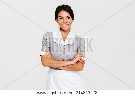 Close-up portrait of young smiling housekeeper in uniform standing with crossed hands and looking at camera, isolated on white background