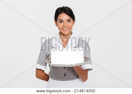 Portrait of ypung smiling female waiter in uniform holding metal tray with empty invitation while standing and looking at camera, isolated over white background