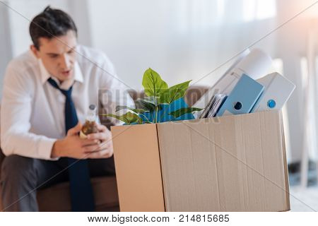Again jobless. Depressed young specialist sitting with a bottle of beer in his hands and a big carton box by his side and feeling terrible after losing one more job