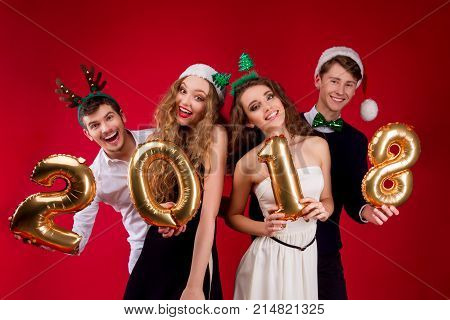 Friends celebrating New Year 2018. Young persons: males / men / boys and females / women / girls in Santa decorated deer horn hats holding gold balloons numbers and smiling on red background