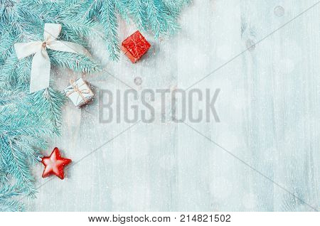 Christmas background. Christmas toys blue fir tree branches on the wooden background. Christmas still life with free space for text. Festive Christmas background. Colorful Christmas holiday card