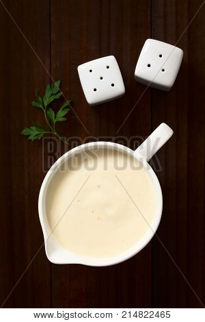 Homemade French Bechamel or White Sauce served in sauce boat photographed overhead on dark wood with natural light (Selective Focus Focus on the sauce)