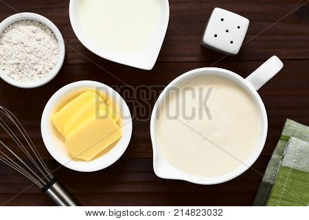 Homemade French Bechamel or White Sauce served in sauce boat with ingredients on the side (flour butter milk) photographed overhead on dark wood with natural light (Selective Focus Focus on the sauce)
