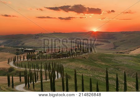 Tuscany, Italy - May 26, 2017: Magnificent spring landscape at sunset.Beautiful view of typical tuscan farm house, green wave hills, cypresses trees, magical sunlight, beautiful golden fields and meadows.