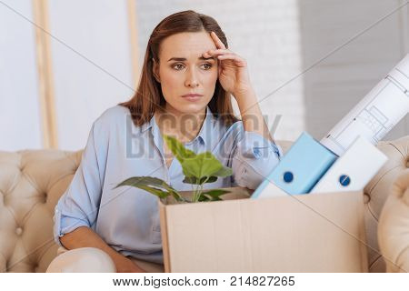 Bad day. Calm tired jobless woman sitting on the sofa near a big box with documents and thinking about the strange situation happening in her life