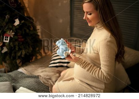 Pregnant woman sits before Christmas tree and looks at baby's bootees. She keeps them in hands.