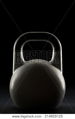 Backlit competition kettlebell silhouette on a black background with text / writing / copy space on and above kettlebell