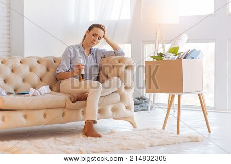Alcohol helps. Unhappy jobless depressed woman sitting in her living room and drinking alcohol while feeling unwell and being in a bad mood