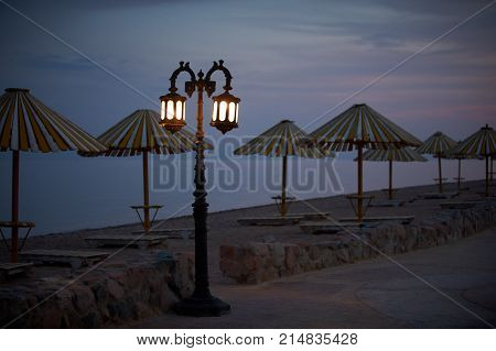 Empty embankment with straw umbrellas and streetlights in Dahab at night.