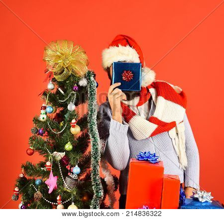 Man With Beard Hides Face On Red Background.