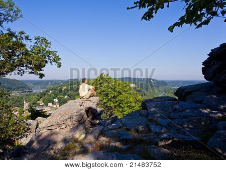 Senior male hiker overlooking the shenandoah and potomac rivers by the town of Harpers Ferry poster