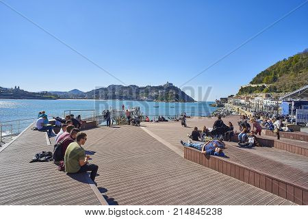 San Sebastian (Donostia) Spain - March 16, 2017. People enjoying a sunbathing in footbridge of leisure harbour of San Sebastian with Santa Clara island and Monte Igueldo in background. Basque Country Guipuzcoa. Spain.