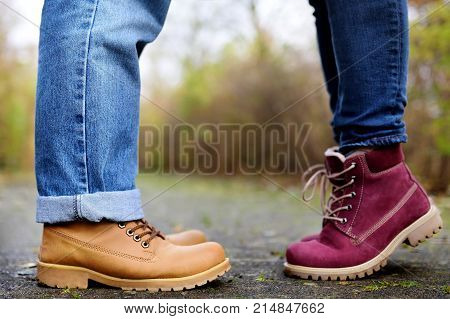 Closeup photo of male and female legs during a date in autumn park. Love couple romantic concept