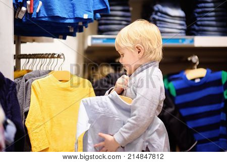 Cute Little Boy Choosing New Clothes During Shopping