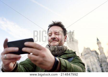 Handsome Milddle Age Man Making A Self Portrait (selfie) With Famous Royal Castle Neuschwanstein On