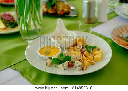 Cheese plate on a white table. Many kinds of cheese on a plate
