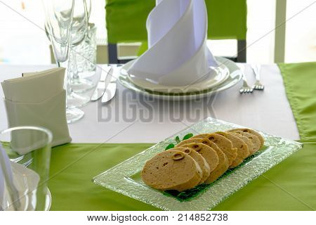 Traditional Jewish passover food gefilte fish with carrots, parsley, horseradish, and lettuce on white linen table cloth with matzah in background