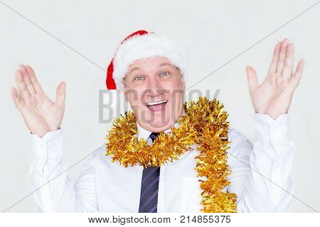 Cheerful amazed businessman winning Christmas giveaway and excited about coming holidays. Positive mature male manager in costume shrugging shoulders because of shock. Success concept