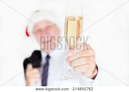 Close-up of businessman holding champagne flute while saying toast at office party. Man raising full flute. Alcohol concept