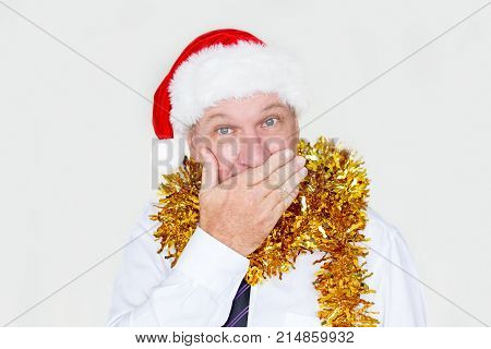 Shocked businessman covering mouth as symbol of silence and looking at camera. Astonished mature male employee in Santa hat surprised with Christmas giveaway. Secret concept