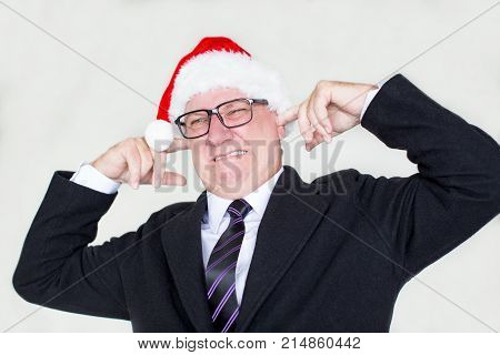 Sullen businessman in Santa hat annoyed with noise and covering ears with fingers. Unhappy mature man in Santa hat tired from Christmas. Irritation concept