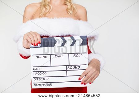 Close-up of sexy young Caucasian woman wearing Santa dress holding clapperboard. Christmas and Film production concept