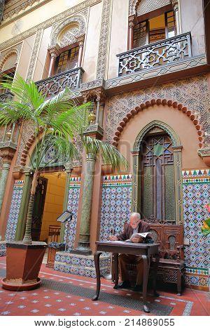 LISBON, PORTUGAL - NOVEMBER 4, 2017: An old man reading inside the courtyard of Casa do Alentejo in Bairro Alto neighborhood