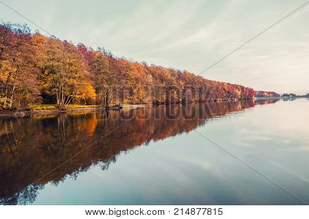 Beautiful lake and colorful forest in autumn evening light. Beautiful forest of colorful autumn trees reflecting in calm lake in Duchonka (Slovakia). Fall season. Scenic view of pond in autumn.