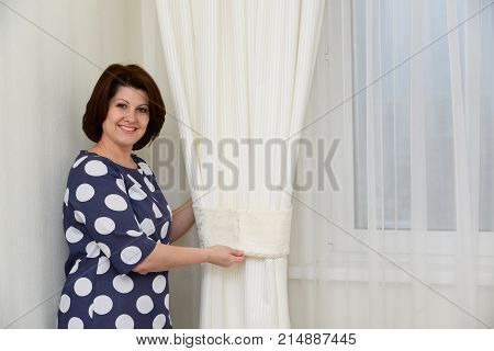 Woman puts a clamps on the curtains