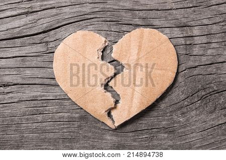 End of love Rupture of relationships. Paper heart broken in half on a wooden background