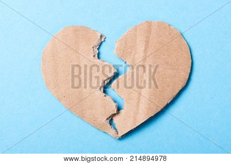End of love Rupture of relationships. Paper heart broken in half on a blue background