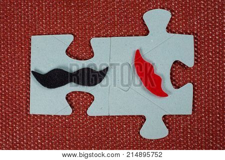 Close-up Of 2 Pieces Of A Puzzle. A Symbolic Man With A Mustache And A Woman With Lips. The Concept