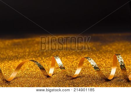 Curly golden serpentine on shiny glitter on black background, copy space. Christmas and new year holiday concept. Bright luxury celebration backdrop