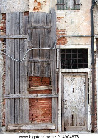 abandoned board up derelict house with padlocked door and decaying brick walls in italy