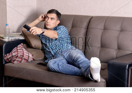 A Young Man In Jeans, With A Remote Control For The Tv Boredom On The Face Changes The Channel