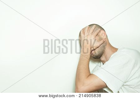 Young depressed man suffering from anxiety and feeling miserable cover his face with his hands and cry leaning on the white wall