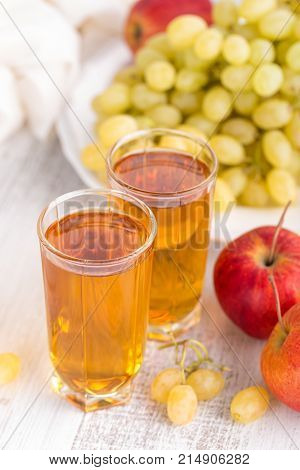 Apple and grape juice in glass on white background closeup