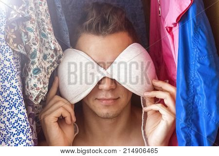 A young man hiding in the closet among women's clothing. Lover in the closet.