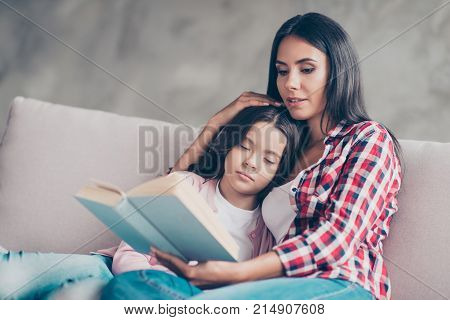 Caring Young Mother In Casual Clothes Is Reading A Story From A Book To Her Cute And Lovely Schoolgi