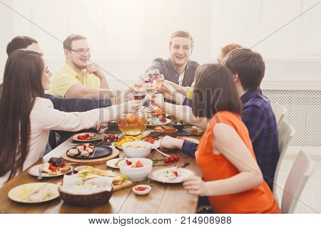People clink glasses, saying cheers at party dinner table in cafe, restaurant or at home. Young cute friends company celebrate with organic food at wooden table indoors.