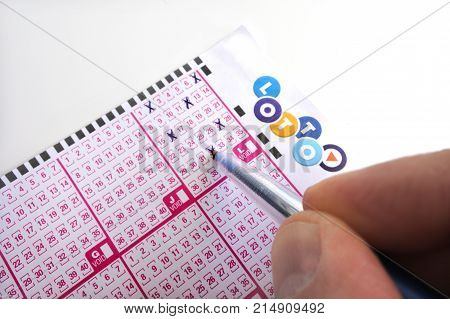 AUCKLAND - NOV 15 2017:Person holds a pen filling in numbers on a lottery ticket. About 70 percent of lottery winners lose or spend all their money in five years or less.