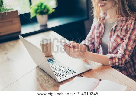 Cropped Shot Of A Young, Smiling Woman Working From Home At Her Desk Using Smart Phone And Notebook