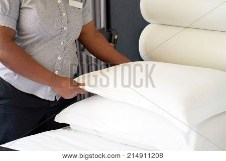 Maid making bed in hotel room. Maid Making Bed