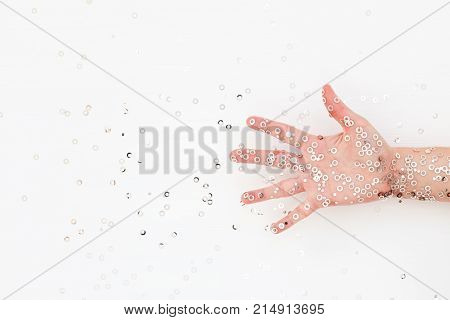 Eccentric Female palm in silver confetti. White holiday background with sparkles. Celebration party concept. Expressive hand. Top view.