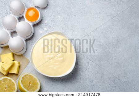 Homemade basic french sauce hollandaise in a white bowl with ingredients butter lemon eggs on a light blue slate stone background with copy space top view
