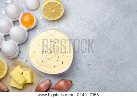 Homemade basic french sauce bearnaise in a white bowl with ingredients butter shallot lemon eggs on a light blue stone background with copy space top view