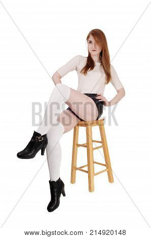 A lovely brunette woman sitting on chair in shorts and long white socks and high heels with legs crossed isolated for white background