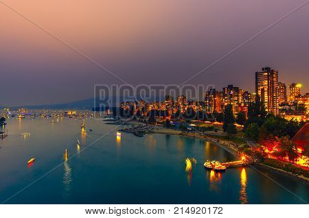 Shooting from the top. City lights of the night metropolis on the ocean with ships and boats floating on the water the coastal line of city beaches groups of people resting on the shore and the mountain and residential high-rise buildings in the backgroun